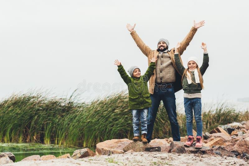 πατέρας και παιδιά με τα αυξημένα χέρια υπαίθρια στοκ φωτογραφίες με δικαίωμα ελεύθερης χρήσης