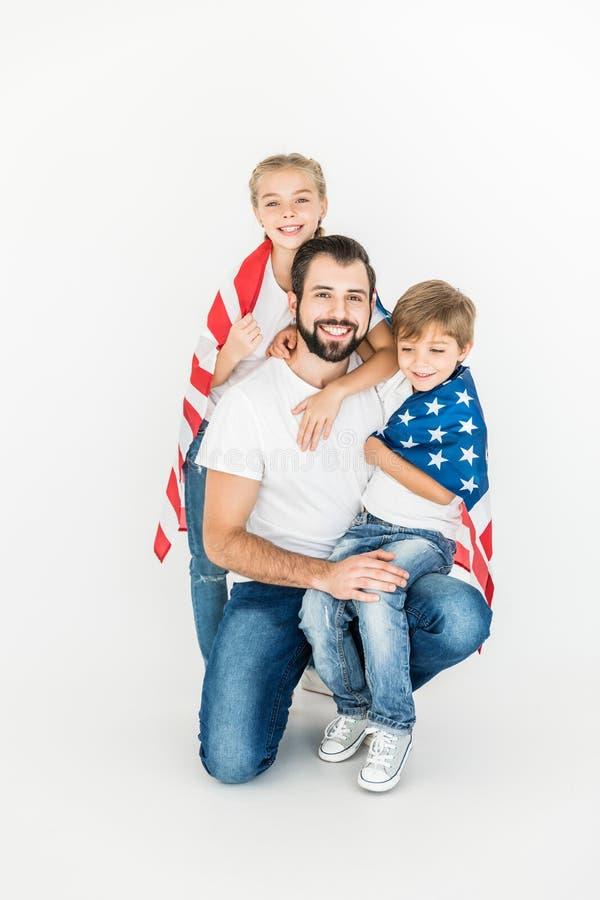 Πατέρας και παιδιά με τη αμερικανική σημαία στοκ εικόνες