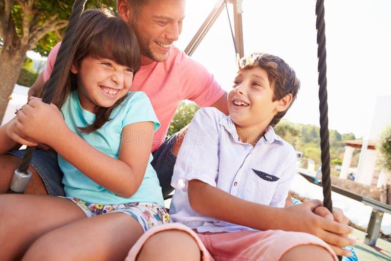Πατέρας και παιδιά που έχουν τη διασκέδαση στην ταλάντευση στην παιδική χαρά στοκ εικόνες
