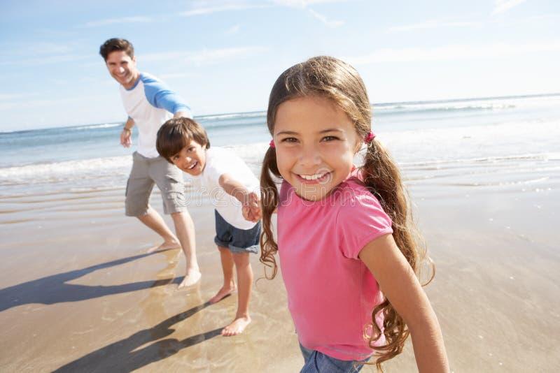 Πατέρας και παιδιά που έχουν τη διασκέδαση στις παραθαλάσσιες διακοπές στοκ εικόνα με δικαίωμα ελεύθερης χρήσης