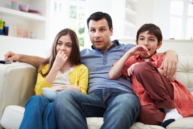 Πατέρας και παιδιά που κάθονται στον καναπέ που προσέχει τη TV από κοινού στοκ φωτογραφία με δικαίωμα ελεύθερης χρήσης
