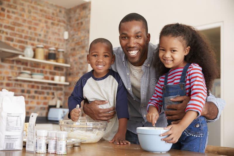 Πατέρας και παιδιά που ψήνουν τα κέικ στην κουζίνα από κοινού στοκ εικόνα
