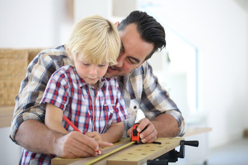Πατέρας και το μικρό παιδί του που εργάζονται στα diy προγράμματα στοκ φωτογραφία με δικαίωμα ελεύθερης χρήσης