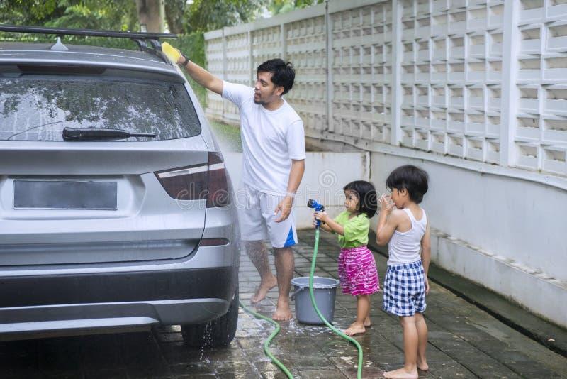 Πατέρας με τα παιδιά που πλένουν ένα αυτοκίνητο στοκ φωτογραφία με δικαίωμα ελεύθερης χρήσης