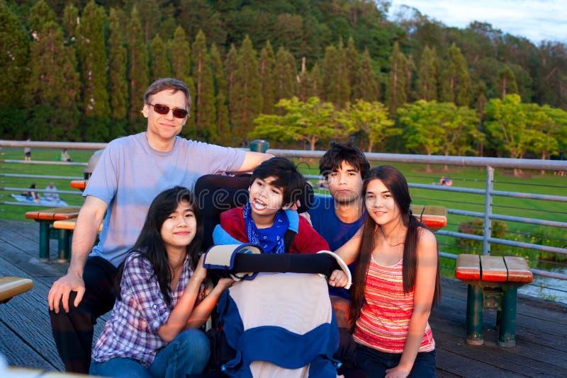 Πατέρας με τα παιδιά στο πάρκο, να περιβάλει με ειδικές ανάγκες γιος στο wheelc στοκ εικόνα