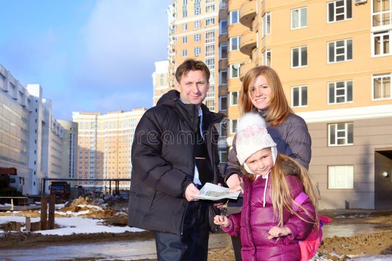 Πατέρας με τα σχέδια των διαμερισμάτων, της κόρης και του realtor στοκ φωτογραφία