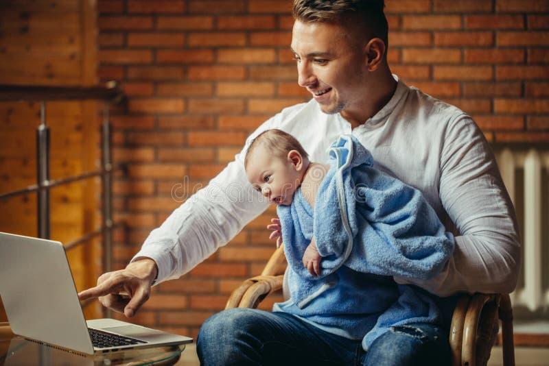 Πατέρας με τη νεογέννητη εργασία μωρών από το σπίτι που χρησιμοποιεί το lap-top στοκ εικόνα με δικαίωμα ελεύθερης χρήσης