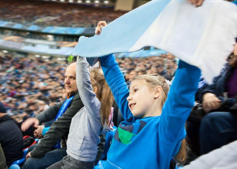 Πατέρας με τον ανεμιστήρα δύο κορών στο ποδοσφαιρικό παιχνίδι, θολωμένο υπόβαθρο στοκ φωτογραφία
