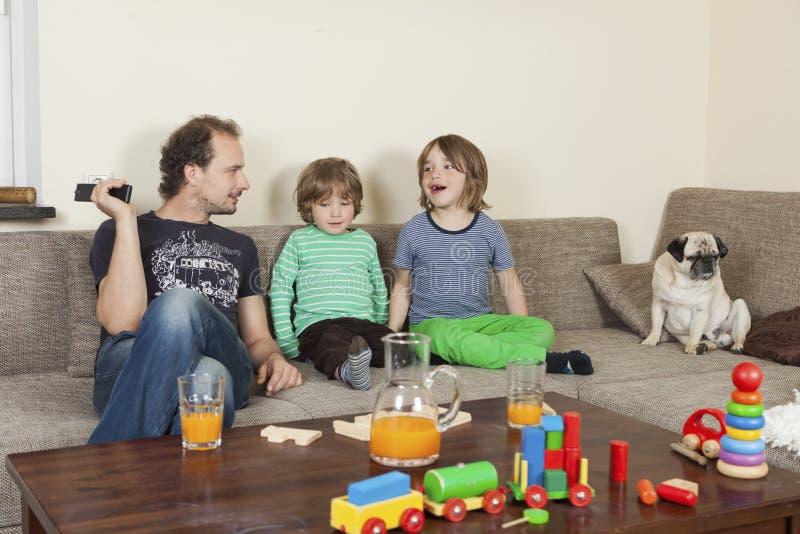 Πατέρας με τους γιους και το σκυλί στον καναπέ στοκ φωτογραφία