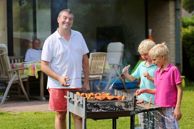 Πατέρας με τους γιους που ψήνουν το κρέας στον κήπο στη σχάρα στοκ φωτογραφίες με δικαίωμα ελεύθερης χρήσης