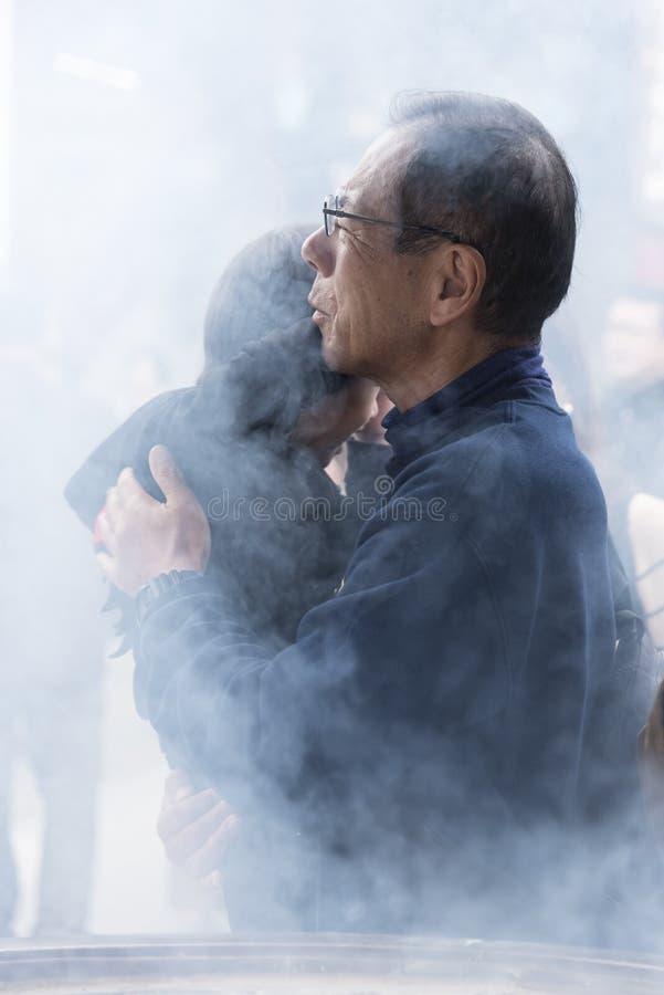 Πατέρας με το παιδί στον καπνό θυμιάματος στοκ φωτογραφία
