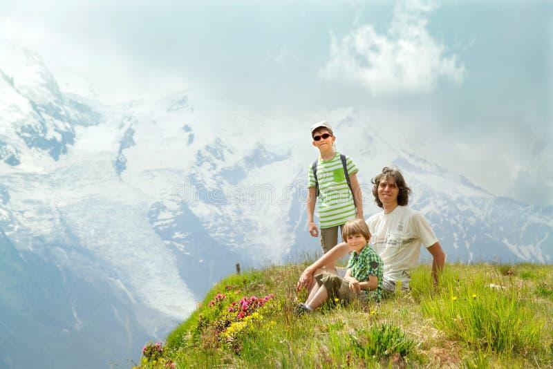 Πατέρας με δύο παιδιά που κάθονται σε έναν απότομο βράχο στοκ φωτογραφία