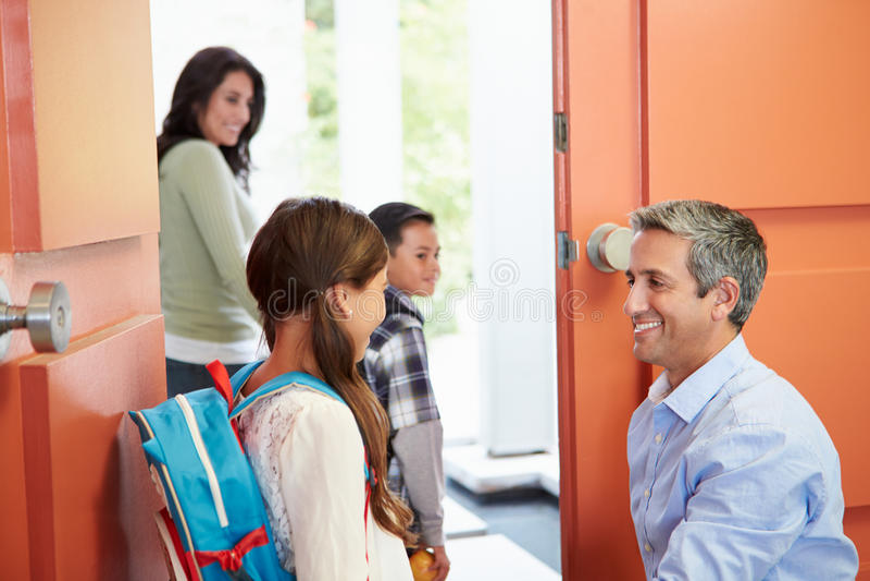 Πατέρας που λέει αντίο στα παιδιά όπως φεύγουν για το σχολείο στοκ εικόνες