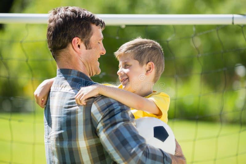 Πατέρας που αγκαλιάζει το γιο στο πάρκο στοκ φωτογραφίες με δικαίωμα ελεύθερης χρήσης