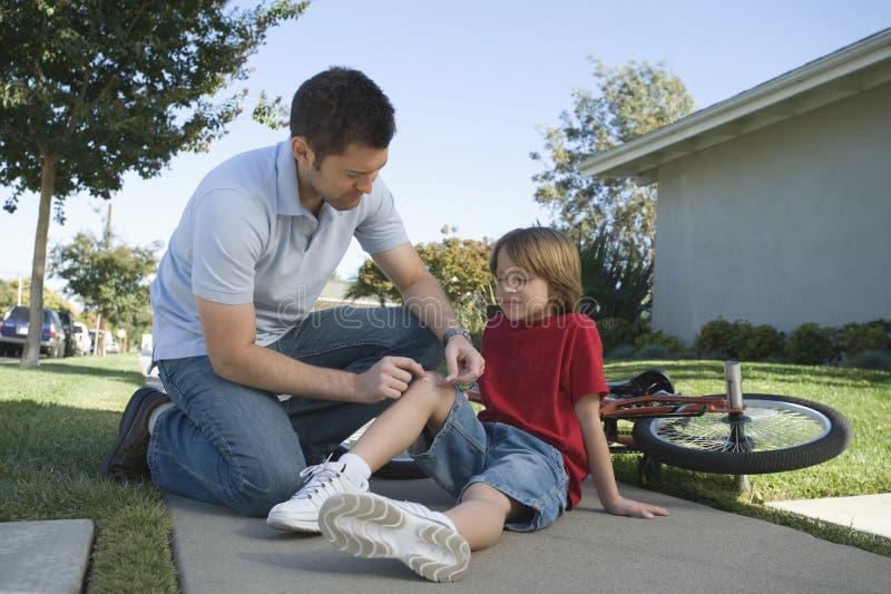 Πατέρας που βάζει το ασβεστοκονίαμα στο γόνατο του γιου υπαίθρια στοκ φωτογραφία