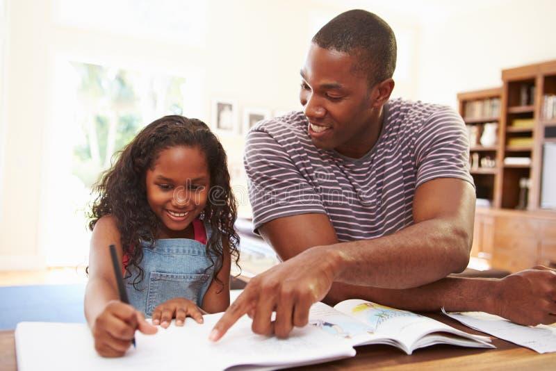Πατέρας που βοηθά την κόρη με την εργασία στοκ εικόνες