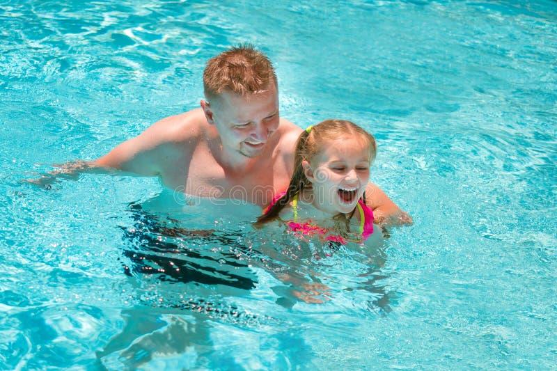 Πατέρας που διδάσκει την κόρη του για να κολυμπήσει στην πισίνα στοκ εικόνες με δικαίωμα ελεύθερης χρήσης