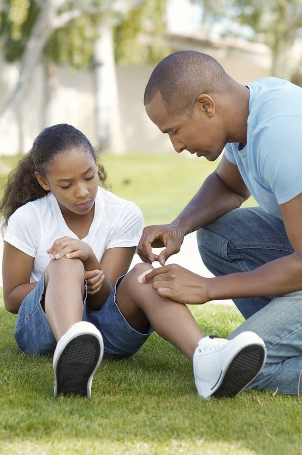 Πατέρας που εφαρμόζει τον επίδεσμο στο γόνατο της κόρης στοκ εικόνα