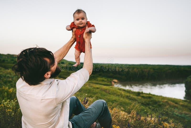 Πατέρας που κρατά ψηλά τον υπαίθριο ευτυχή οικογενειακό τρόπο ζωής μωρών στοκ εικόνες
