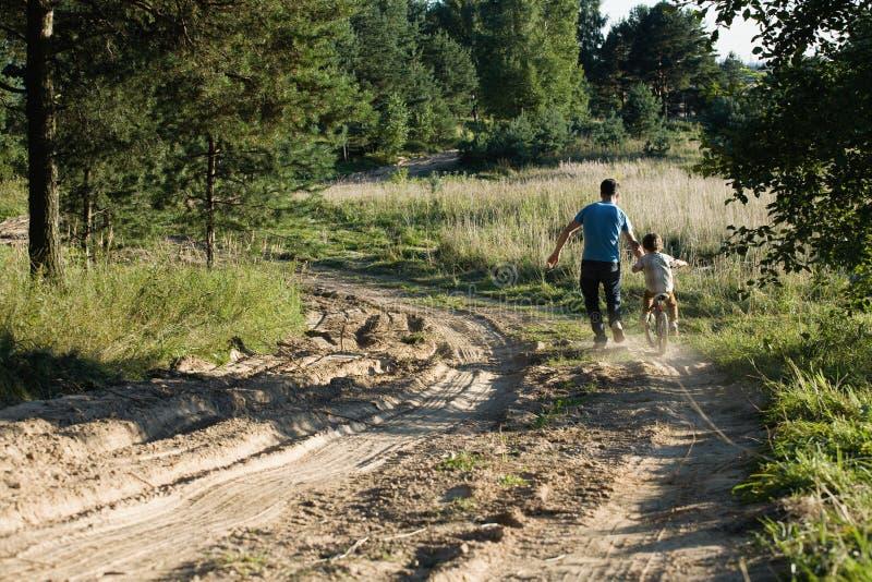 Πατέρας που μαθαίνει το γιο του για να οδηγήσει στο ποδήλατο έξω στοκ εικόνες