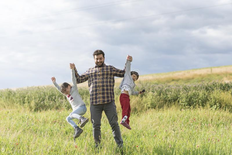 Πατέρας που παίζει ανυψωτικός την κόρη και το γιο του στοκ εικόνα με δικαίωμα ελεύθερης χρήσης