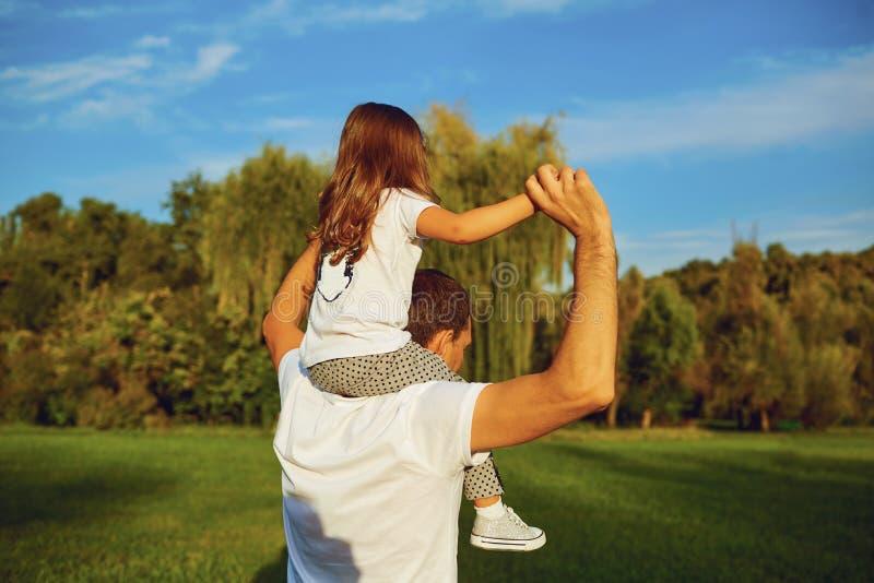 Πατέρας που παίζει και που φέρνει την κόρη του στους ώμους στοκ φωτογραφίες