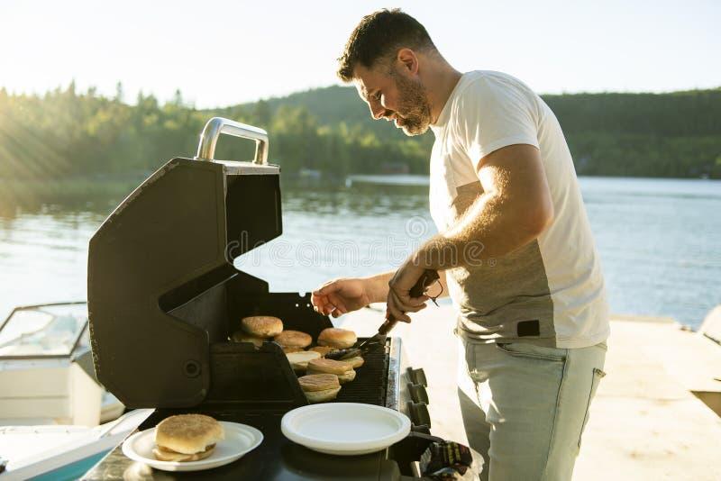 Πατέρας που προετοιμάζει το χάμπουργκερ σε μια σχάρα υπαίθρια κοντά σε μια λίμνη στοκ φωτογραφία