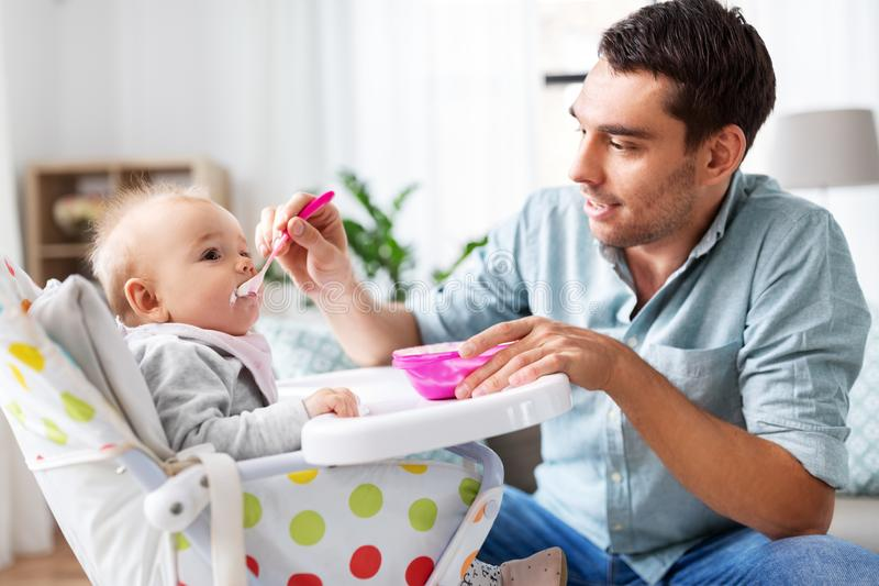 Πατέρας που ταΐζει το ευτυχές μωρό στο highchair στο σπίτι στοκ φωτογραφία με δικαίωμα ελεύθερης χρήσης