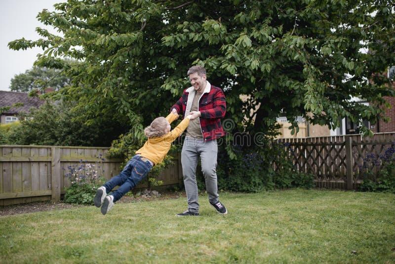 Πατέρας που ταλαντεύεται το γιο του γύρω από το εξωτερικό στοκ φωτογραφίες