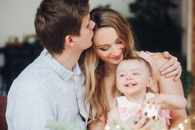 Πατέρας που φιλά την όμορφη ξανθή σύζυγο, η οποία εκμετάλλευση σε ετοιμότητα λίγη χαριτωμένη κόρη στοκ φωτογραφία