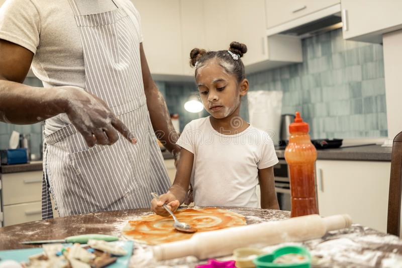 Πατέρας που φορά τη ριγωτή ποδιά που διδάσκει το μικρό κορίτσι του που κατασκευάζει την πίτσα στοκ φωτογραφία