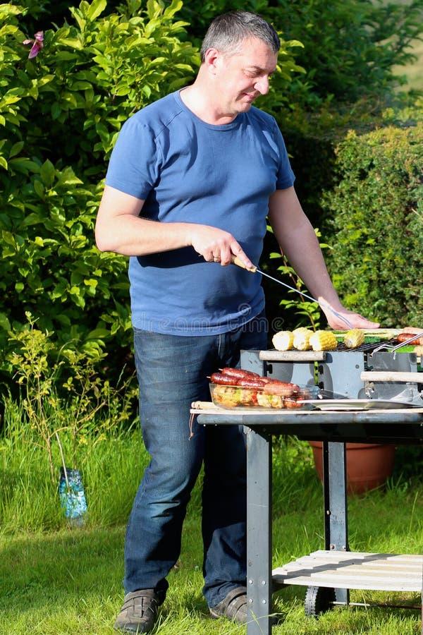 Πατέρας που ψήνει το κρέας στον κήπο για το μεσημεριανό γεύμα στη σχάρα στοκ φωτογραφία με δικαίωμα ελεύθερης χρήσης