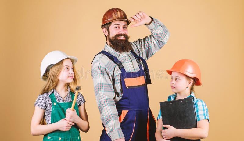 Πατέρες και κορίτσια επισκευάζουν το σπίτι Διδάξτε την κόρη Άτυπη εκπαίδευση Ημέρα των πατέρων Αδερφές βοηθούν τον πατέρα να χτίσ στοκ φωτογραφία