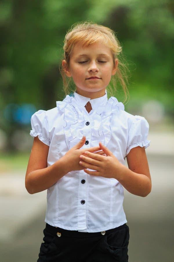Πατριωτικός λίγη χαριτωμένη μαθήτρια στη σχολική στολή που ακούει το εθνικό ύμνο στοκ φωτογραφία με δικαίωμα ελεύθερης χρήσης