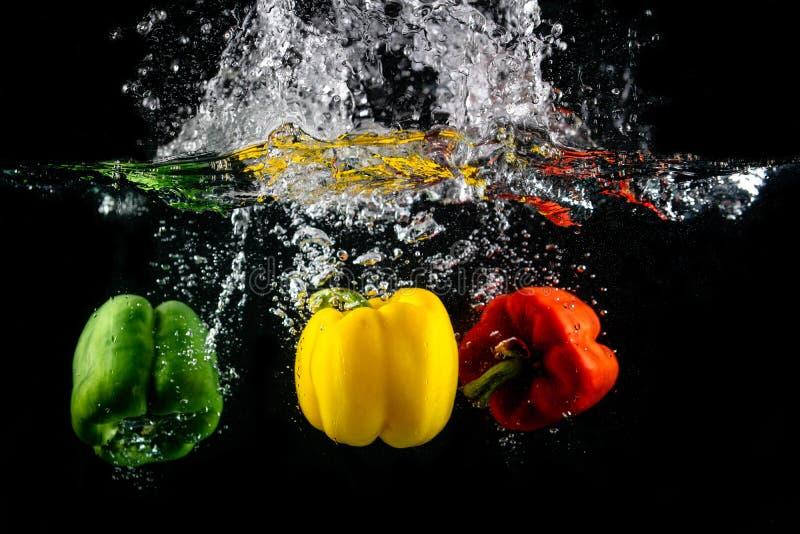 Παφλασμός πάπρικας τρία στο νερό στο μαύρο υπόβαθρο, καψικό annuum: πιπέρι κουδουνιών και buble στοκ εικόνα με δικαίωμα ελεύθερης χρήσης
