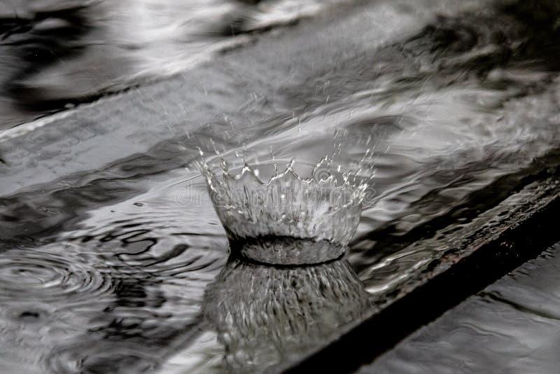 Παφλασμός πτώσης βροχής στο ξύλινο πάτωμα που αναπηδά και που διαμορφώνει μια κορώνα νερού στοκ εικόνες
