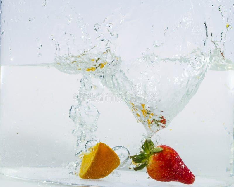 Παφλασμός φραουλών και εσπεριδοειδών στο νερό στοκ εικόνες