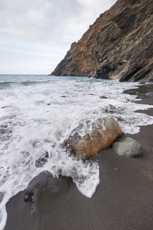 Παφλασμός ψεκασμού κυμάτων πέρα από τη δύσκολη παραλία μια θυελλώδη ημέρα στο Λα Gomera στοκ φωτογραφία