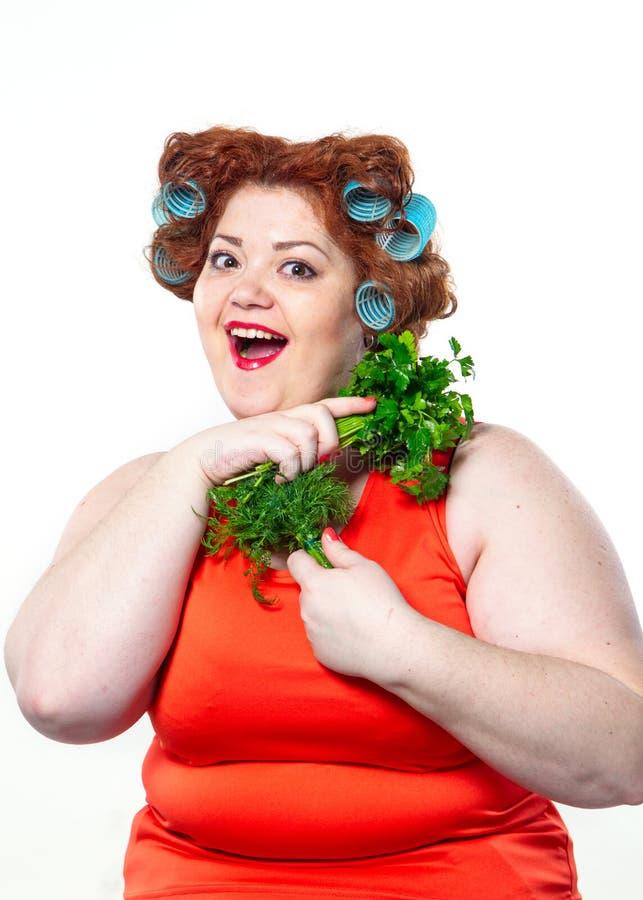 Παχιά γυναίκα με το κόκκινο κραγιόν αισθησιασμού στα ρόλερ σε έναν μαϊντανό και έναν άνηθο εκμετάλλευσης διατροφής στοκ εικόνα
