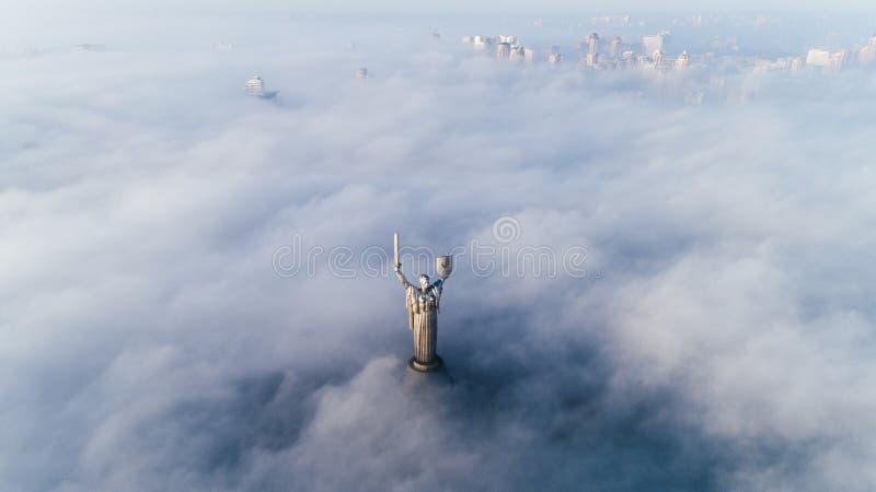Παχιά σύννεφα της ομίχλης φθινοπώρου και του μνημείου μητέρας πατρίδας που κολλά από τους στοκ φωτογραφία