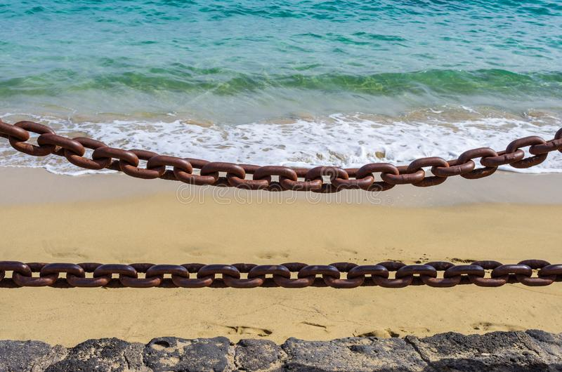 Παχιές σκουριασμένες αλυσίδες με τη θάλασσα στο υπόβαθρο στοκ εικόνες
