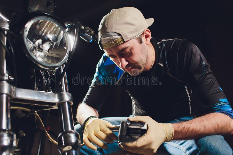 Ποδήλατο καθορισμού ατόμων Βέβαιος νεαρός άνδρας που επισκευάζει τη μοτοσικλέτα κοντά στο γκαράζ του παχυμετρικός διαβήτης, αντικ στοκ φωτογραφίες με δικαίωμα ελεύθερης χρήσης