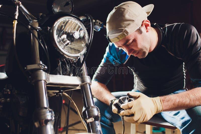 Ποδήλατο καθορισμού ατόμων Βέβαιος νεαρός άνδρας που επισκευάζει τη μοτοσικλέτα κοντά στο γκαράζ του παχυμετρικός διαβήτης, αντικ στοκ εικόνες με δικαίωμα ελεύθερης χρήσης