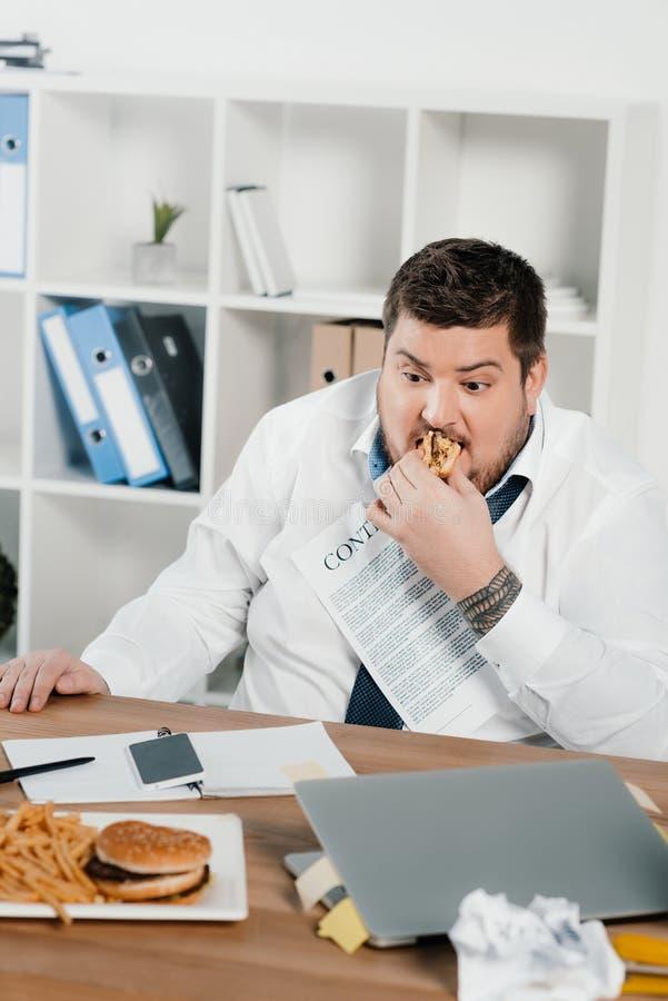 παχύς επιχειρηματίας που τρώει τα χάμπουργκερ και τις τηγανιτές πατάτες στοκ εικόνες με δικαίωμα ελεύθερης χρήσης