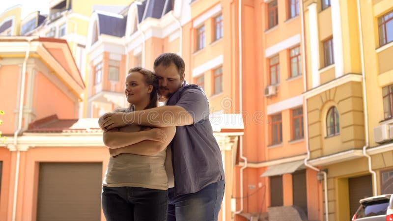 Παχύσαρκη αρσενική αγκαλιάζοντας ντροπαλή φίλη, πλήρης εμπιστοσύνης σχέση ζευγών, αβεβαιότητες στοκ φωτογραφίες