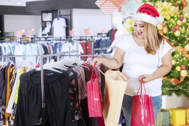 Παχύσαρκη γυναίκα που εξετάζει τα δώρα Χριστουγέννων της στοκ εικόνες