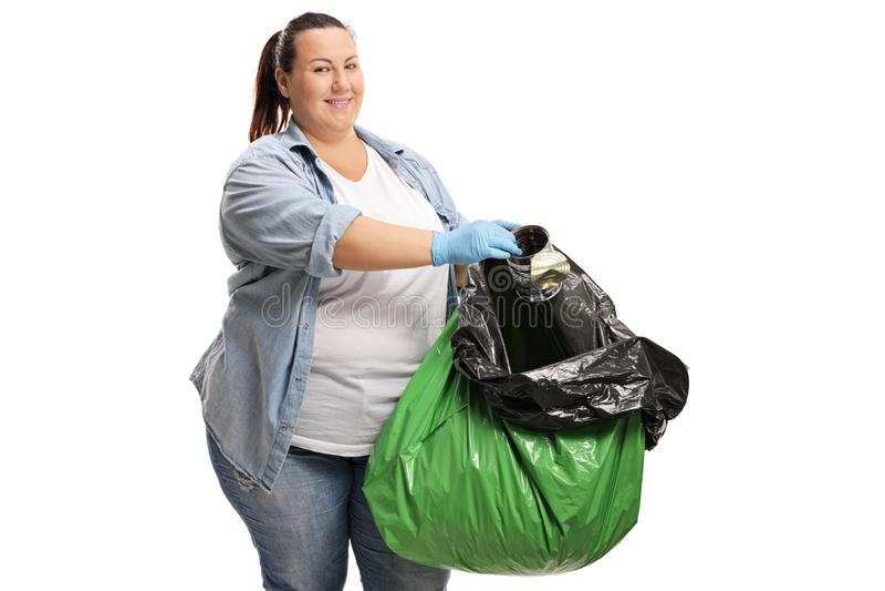 Παχύσαρκη γυναίκα που συλλέγει τα απορρίματα σε μια πλαστική τσάντα στοκ φωτογραφία