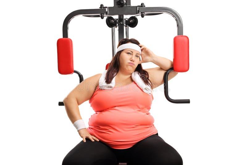 Παχύσαρκη νέα γυναίκα σε μια μηχανή ικανότητας που κουράζεται της άσκησης στοκ εικόνα