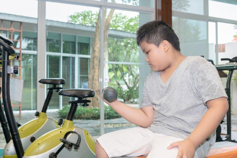 Παχύσαρκος παχύς ανυψωτικός αλτήρας αγοριών στο δωμάτιο ικανότητας στοκ εικόνες με δικαίωμα ελεύθερης χρήσης