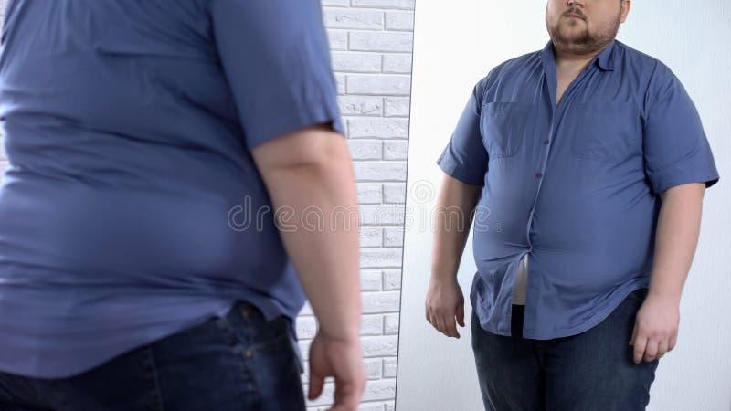 Παχύσαρκο άτομο που φορά το σφιχτό πουκάμισο, υπεργέθες πρόβλημα ιματισμού, αβεβαιότητες στοκ εικόνες